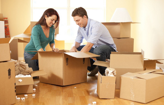 couple packing boxes together before moving