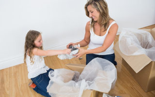 mother and daughter packing glassware in boxes