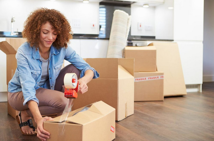 woman packing fragile items for storage